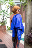 Female beauty concept. Portrait of fashionable young girl in blue luxury snakeskin python jacket and sunglasses posing Royalty Free Stock Photo