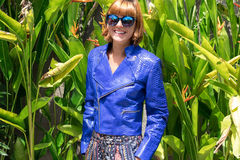 Female beauty concept. Portrait of fashionable young girl in blue luxury snakeskin python jacket and sunglasses posing Royalty Free Stock Photography