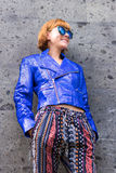 Female beauty concept. Portrait of fashionable young girl in blue luxury snakeskin python jacket and sunglasses posing Stock Photography