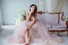 Female beauty. Luxury woman portrait with perfect hair and make-up. Attractive young lady in elegant dress posing in. Sensual way on sofa Stock Image