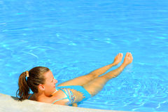 Female beauty relaxing in the swimming pool Royalty Free Stock Photography