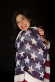 Female beauty wrapped in an American flag smiling Stock Image