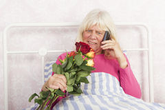 Female in bed with roses and telephone Royalty Free Stock Photography