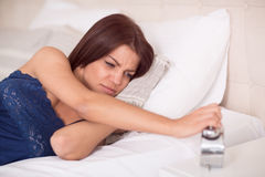 Female in bed sullenly look at clock Stock Images