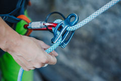 Female belayer with the rope and carabines. Royalty Free Stock Photo