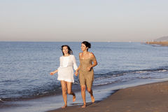 Female best friends on the beach. Two women running on the beach stock photo