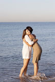 Female best friends on the beach. Two women hugging on the beach royalty free stock image