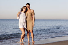 Female best friends on the beach. Two women standing on the beach royalty free stock photo