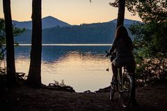 Female on a bicycle enjoying the view of the sea with mountains in the background stock photo