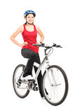 Female bicyclist on a bicycle. Full length portrait of a female bicyclist posing on a bicycle against white background stock image