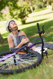 Female bicyclist with hurt leg sitting in park Stock Photos