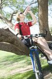 Female Bicyclist Sitting On Tree While Drinking Water Stock Image