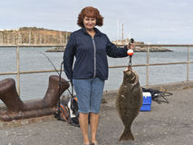 Female with the big fish. Woman holding a 17 pound Halibut royalty free stock images
