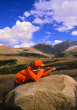 Female Big Game Hunter. A female big game hunter with rifle up looking through her scope in the high country Royalty Free Stock Photos