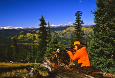Female Big Game Hunter. A female big game hunter with rifle up looking through her scope in the high country Stock Image