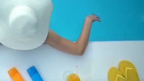 Female in big white hat playing with water in swimming pool, vacation in hotel. Stock footage stock video