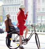 Female biker. In a red suit and a white hat royalty free stock photos