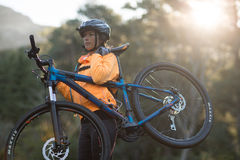Female biker carrying mountain bike Stock Photos