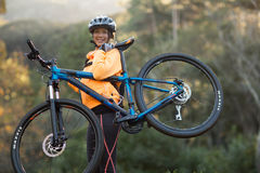 Female biker carrying mountain bike Royalty Free Stock Photo