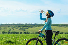 Female biker, drinking water bottle Royalty Free Stock Image