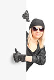 Female biker giving thumb up behind a panel Stock Photo