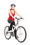Female biker with helmet posing next to a bike. Against white background Royalty Free Stock Photos