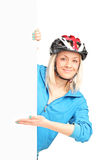 Female biker with helmet standing behind a panel Royalty Free Stock Images