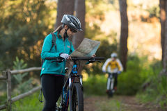 Female biker looking at a map with mountain bike Stock Images