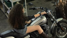 Female biker poses on the chopper at the motorcycle workshop stock video