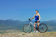 A female biker posing with a mountain bike Royalty Free Stock Image