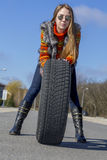 Female biker rolls big wheel Stock Image
