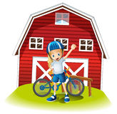 A female biker standing in front of the red barnhouse Royalty Free Stock Image
