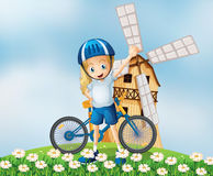 A female biker standing at the hilltop with a windmill Royalty Free Stock Photo