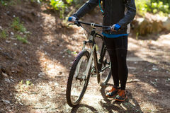 Female biker standing with mountain bike on dirt track Royalty Free Stock Photography