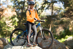 Female biker standing with mountain bike in forest Stock Images