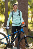 Female biker standing with mountain bike in forest Royalty Free Stock Photos
