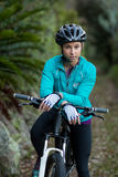 Female biker standing with mountain bike in forest Royalty Free Stock Images