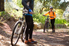 Female biker walking with mountain bike on dirt track Royalty Free Stock Images