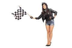 Female biker waving a checkered race flag Royalty Free Stock Photography