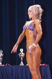Female bikini contestant shows het best front pose on stage Stock Images