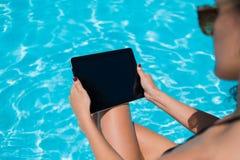 Female in bikini watching video on digital tablet while sunbathe in hotel Royalty Free Stock Photos