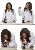 Female Bio Engineer or Medical Student. Black female scientist wearing a lab coat with microscope and petri dish doing micro biology research.  She is working in Stock Photo