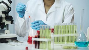 Female biochemist working at laboratory, taking sample of liquid from the flask Royalty Free Stock Photos