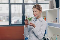 Biologist with fern plant. Female biologist in white coats holding fern plant in laboratory Royalty Free Stock Images