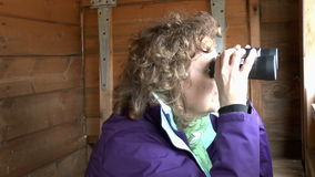 Female Bird watcher. Using a pair of binoculars in a hide looking at birds stock video