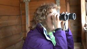 Female Bird watcher. Using a pair of binoculars in a hide looking at birds stock video footage