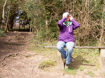 Female Bird watcher. Woman sitting on a wooden bench in the countryside looking through a pair of Binoculars Stock Image