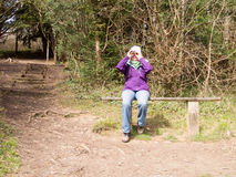 Female Bird watcher. Woman sitting on a wooden bench in the countryside looking through a pair of Binoculars Stock Photo