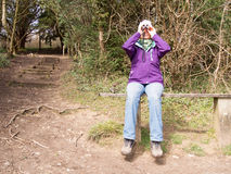 Female Bird watcher. Woman sitting on a wooden bench in the countryside looking through a pair of Binoculars Royalty Free Stock Photography