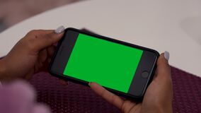 Female black hands uses smartphone with green screen chroma key. Few types of motion - scrolling, tapping, zoom in and
